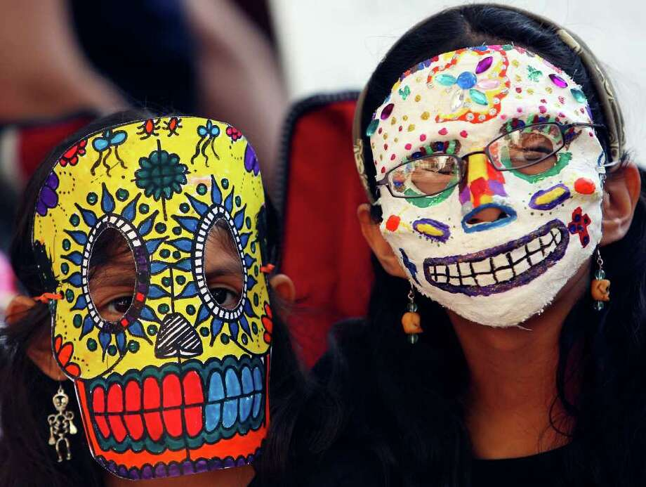 Lilianna (left) and Vivianna Avila-Farias wear Dia de los Muertos mask while attending events in La Villita Sunday Nov. 2, 2008.  (PHOTO BY EDWARD A. ORNELAS/eornelas@express-news.net) Photo: EDWARD A. ORNELAS, SAN ANTONIO EXPRESS-NEWS / eornelas@express-news.net