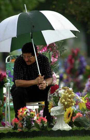 FOR WEB PAGE SLIDE SHOW: Justo Talamantez reflects while sitting vigil by his wife's grave on Dia de