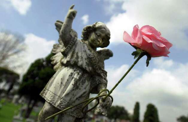 METRO/DAILY: A solitary rose rests in the hand of a statue marking a grave at San Fernando cemetary on el Dia de los Muertos Thursday. Staff Photo By: John Davenport Photo: JOHN DAVENPORT, JD / EN