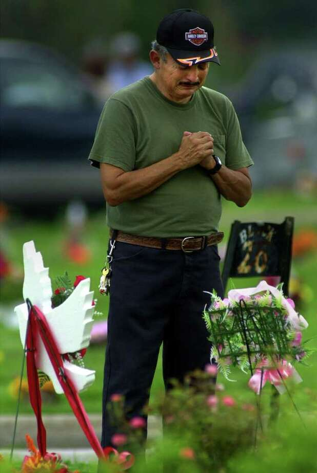 Santiago Rodriguez prays for his deceased wife Maria Esther Rodriguez on el Dia de los Muertos at San Fernando cemetary Thursday.  Photo: JOHN DAVENPORT, JD / EN
