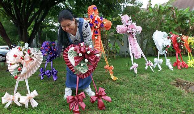 FOR METRO/DAILY/ Day of the Dead:   Josephina Perez arranges several of the colorful wreaths on the curb-side of the Apostolic Church on Cupples Road in preparation for the Dia De Los Muertos Celebration Nov.1, 2000. Many will visit love-ones  and bring flowers near by the San Fernando Cemetary today Photo: DELCIA LOPEZ, EN / EN