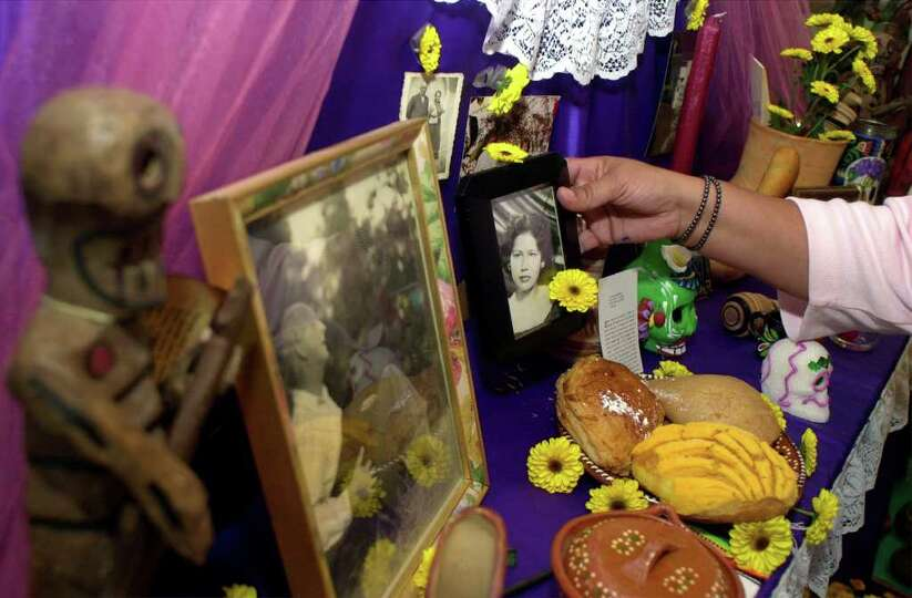 Becky Rush places a picture of her mother on an altar at the Guadalupe Cultural Arts Center gift sho