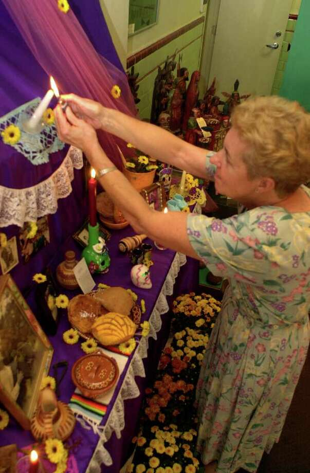 Renee Casabo lights a candle on  Dia de los Muertos altar at the Guadalupe Cultural Arts Center gift shop Friday, October 27, 2000.  Photo: BAHRAM MARK SOBHANI, EN / EN