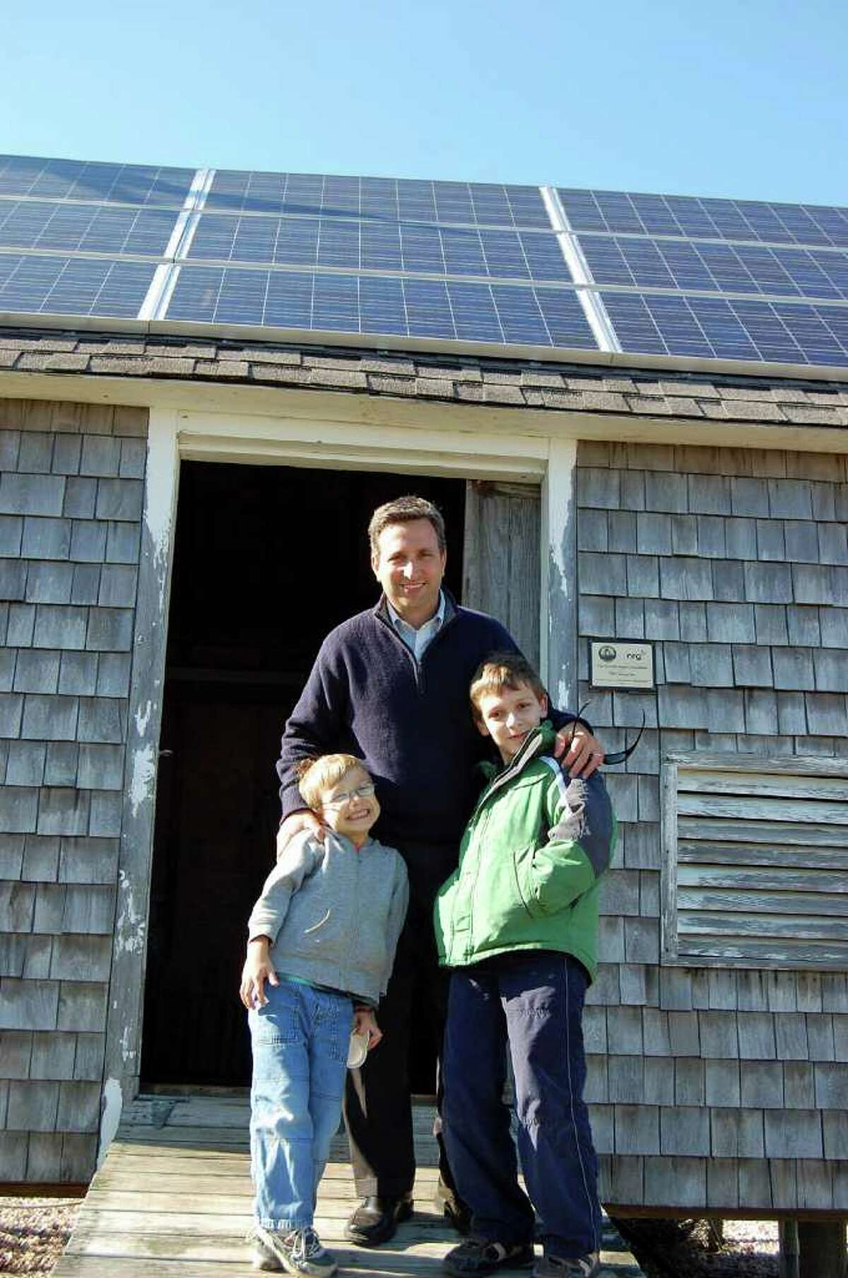 State Sen. Bob Duff (D-Norwalk) and his sons check out the building that houses the solar photovoltaic system, which includes 14 solar panels on its roof, donated by NRG Energy to power the island on Monday. It replaces gasoline-powered generators.