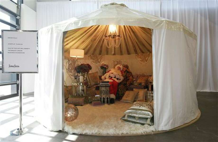 """Sitting inside a plush Rainier Yurt, Brady White portrays Santa Claus, left, as model Brittany Leigh whispers to him as they pose inside the """"Dream Folly"""" gift presented during the unveiling of the Neiman Marcus Christmas catalog in Dallas,  Tuesday, Oct. 18, 2011.  The 18-foot-diameter yurt is a simulation of genie's bottle with a price beginning at $75,000. Photo: Associated Press"""