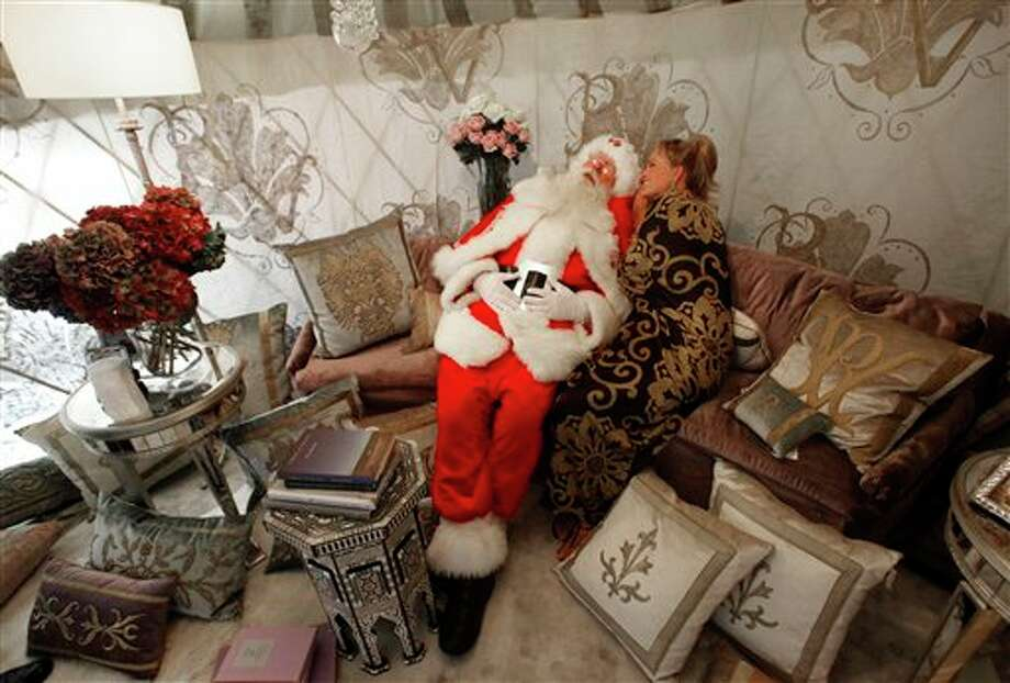 "Sitting inside a plush Rainier Yurt, Brady White portrays Santa Claus, left, as model Brittany Leigh whispers to him as they pose inside the ""Dream Folly"" gift presented during the unveiling of the Neiman Marcus Christmas catalog in Dallas, Tuesday, Oct. 18, 2011. The 18-foot-diameter yurt is a simulation of genie's bottle with a price beginning at $75,000. Photo: Associated Press"