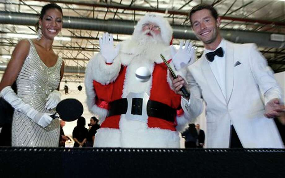 Models Youri Bebik, right, and Carlotta Lennox, left, demonstrate the Tom Burr table tennis table with Brady White portraying Santa Claus, during the unveiling of the Neiman Marcus Christmas catolog in Dallas, Tuesday, Oct. 18, 2011. The limited edition table is sculpted with black rubber and has a price tag of $45,000. Photo: Associated Press