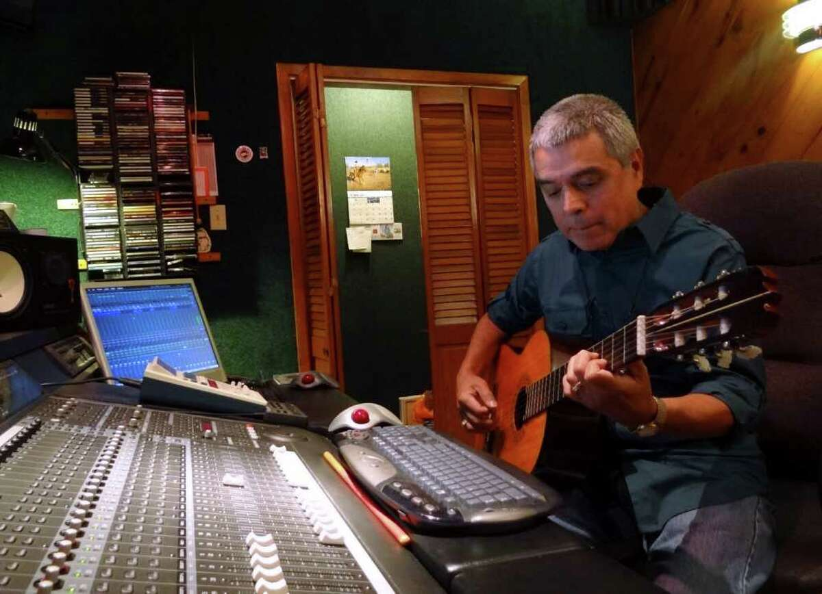 Grammy-winning producer/engineer and musician Gilbert Velasquez plays guitar in his recording studio. He has had a hand in several recent Grammy projects. BILLY CALZADA / EXPRESS-NEWS