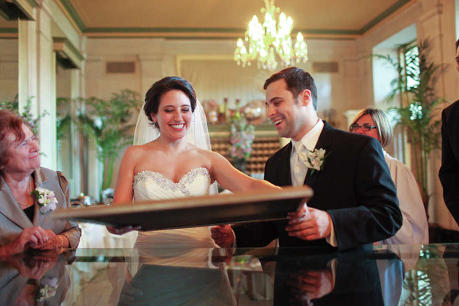 One of the special moments was signing the Ketubah, a Jewish marriage certificate that now hangs in a frame in the couple's apartment. (Photo by Clark+Walker)