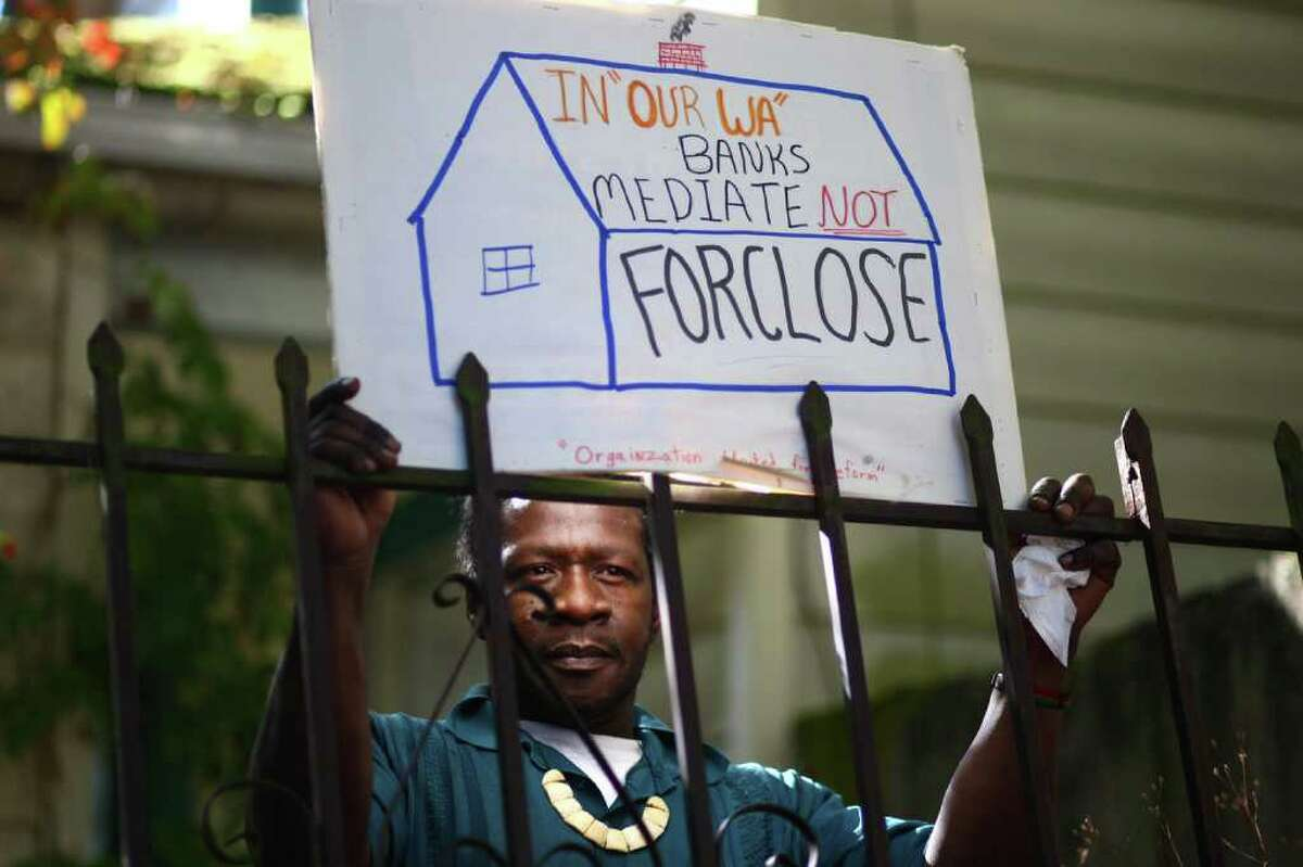 Luster Mitchell, Jr. holds a sign during a rally to support his mom, Dixie Mitchell, 71, on Tuesday, October 18, 2011. Mitchell's home of 44 years is scheduled to go to auction on October 28th after years of battling with Ocwen Financial.