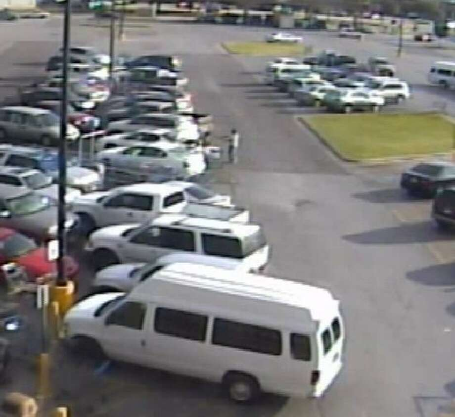 Screenshots from a surveillance video show a man in a white T-shirt (on right) robbing a woman (on left) while she loaded groceries into her car at the Walmart on Dowlen. Photo: Beaumont Police Department