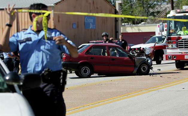 A Houston police officer stretches active scene tape along the 8300 block of Hempsead Rd. where a person in a red Toyota Corolla, which appeared to be involved in a head-on collision with a Ford F-350 pickup truck, died, police said Tuesday, Oct. 18, 2011, in Houston.  There were no other injuries. Photo: Johnny Hanson, Houston Chronicle / © 2011 Houston Chronicle