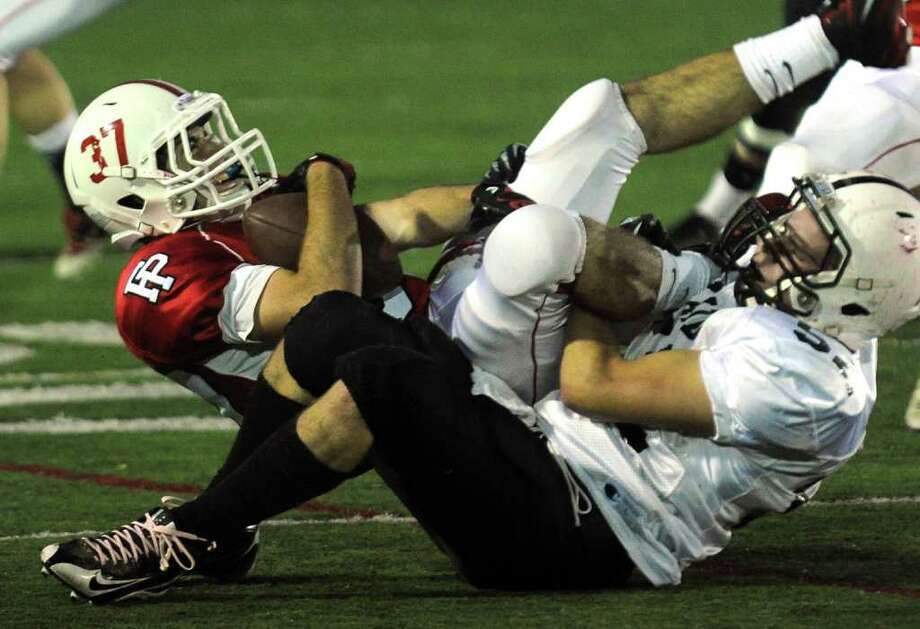 Xavier's Ryan Craig tackles Fairfield Prep's Joe McBride. Photo: Christian Abraham / Connecticut Post