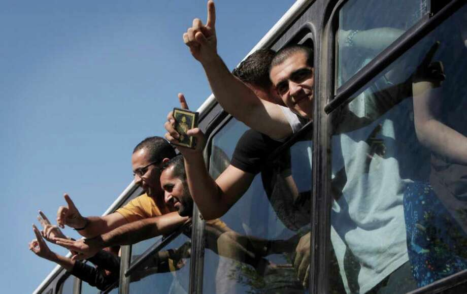 """NASSER NASSER : ASSOCIATED PRESS  GOING HOME: Freed Palestinian prisoners from Israeli jails jubilantly flash """"victory"""" signs as they are transported to freedom in the Gaza Strip. Photo: Nasser Nasser / AP"""