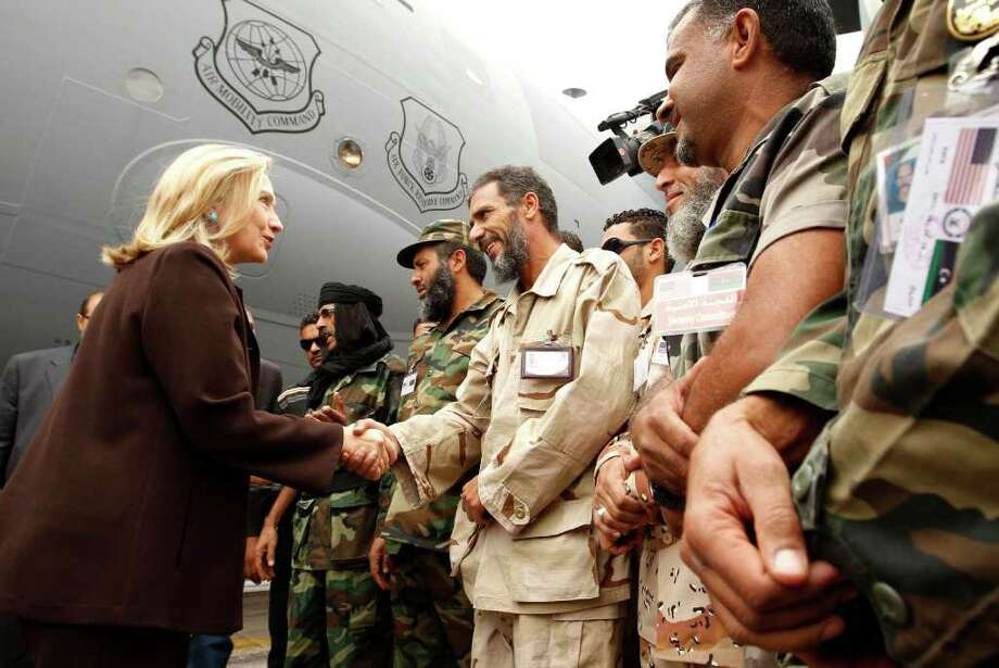 U.S. Secretary of State Hillary Rodham Clinton meets Libyan soldiers at the steps of her C-17 military transport upon her arrival in Tripoli in Libya, Tuesday Oct. 18, 2011. The Obama administration on Tuesday increased U.S. support for Libya's new leaders as Secretary of State Hillary Rodham Clinton made an unannounced visit to Tripoli and pledged millions of dollars in new aid, including medical care for wounded fighters and additional assistance to secure weaponry that many fear could fall into the hands of terrorists.  (AP Photo/Kevin Lamarque, Pool) Photo: KEVIN LAMARQUE / POOL REUTERS