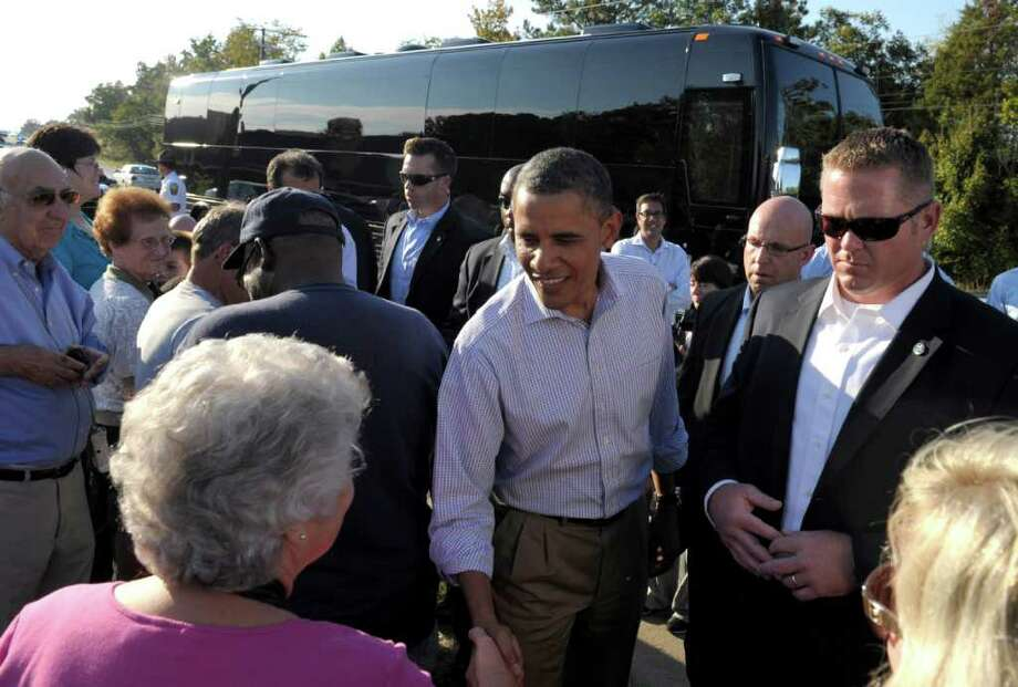President Barack Obama stops to visit with people on the side of the road in Brodnax, Va, Tuesday, Oct. 18, 2011. Obama is on a three-day bus tour promoting the American Jobs Act. (AP Photo/Susan Walsh) Photo: Susan Walsh / AP