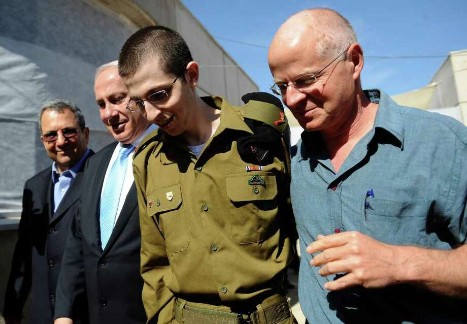 In this photo released by the Israeli Government Press Office, released Israeli soldier Gilad Schalit, is escorted by his father Noam Schalit, right, Prime Minister Benjamin Netanyahu and Defense minster Ehud Barak as he arrives at Tel Nof Air base in southern Israel, Tuesday, Oct. 18, 2011. Looking thin, weary and dazed, the  Israeli soldier returned home Tuesday from more than five years of captivity in the Gaza Strip in exchange for hundreds of Palestinian prisoners whose joyful families greeted them with massive celebrations. Photo: Anonymous, Associated Press