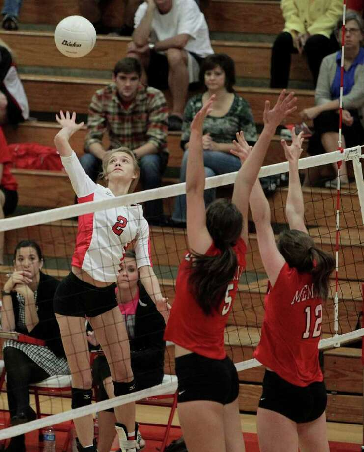 Katy's Mollie Wolf (2) goes up high for a spike attempt as Memorial's Carly Freels (5) and Erika Edrington (12) defend. Photo: Bob Levey, Houston Chronicle / ©2011 Bob Levey