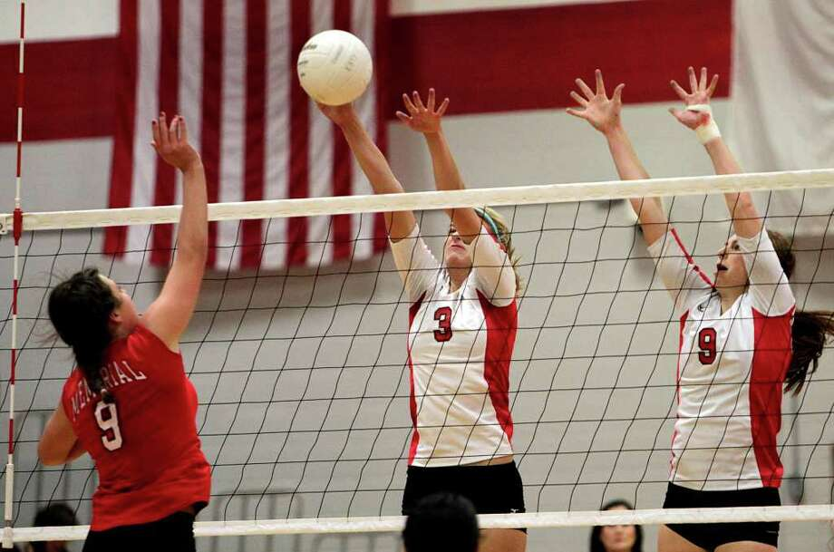 Memorial's Makenzie Borman (9) spikes the ball off the block attempt by Katy's Lydia McKay (3) and Shelby Dawson (9). Photo: Bob Levey, Houston Chronicle / ©2011 Bob Levey