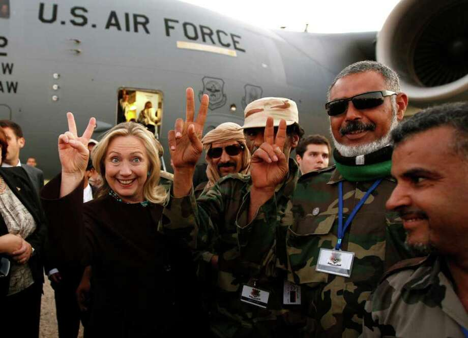 U.S. Secretary of State Hillary Rodham Clinton  gestures with Libyan soldiers upon her departure from Tripoli in  Libya Tuesday, Oct.18, 2011. Photo: Kevin Lamarque, Associated Press / REUTERS POOL