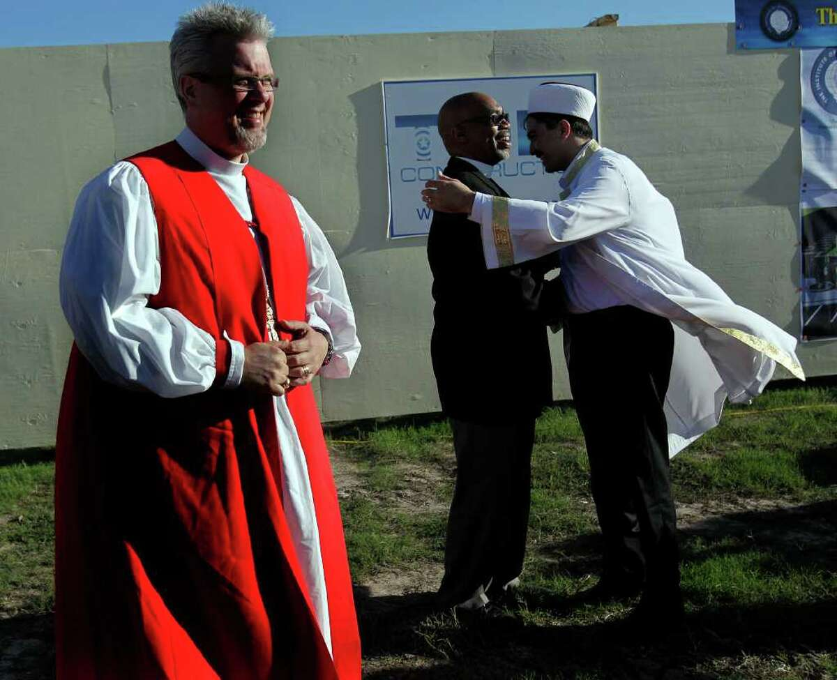 After the groundbreaking for the Interfaith Peace Garden, Imam Mustafa Yigit, right, of Houston Blue Mosque hugs Rev. John Ogletree of the First Metropolitan Church next to The Rt. Rev. C. Andrew Doyle, bishop of the Episcopal Diocese of Texas before more than 200 gathered with Houston area religious and political leaders during a prayer service calling for sensible immigration reform at The Institute of Interfaith Dialog Tuesday, Oct. 18, 2011, in Houston.