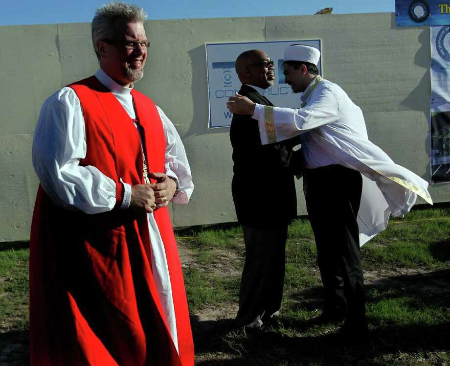 After the groundbreaking for the Interfaith Peace Garden, Imam Mustafa Yigit, right, of Houston Blue Mosque hugs Rev. John Ogletree of the First Metropolitan Church next to The Rt. Rev. C. Andrew Doyle, bishop of the Episcopal Diocese of Texas before more than 200 gathered with Houston area religious and political leaders during a prayer service calling for sensible immigration reform at The Institute of Interfaith Dialog Tuesday, Oct. 18, 2011, in Houston. Photo: Johnny Hanson, Houston Chronicle / © 2011 Houston Chronicle