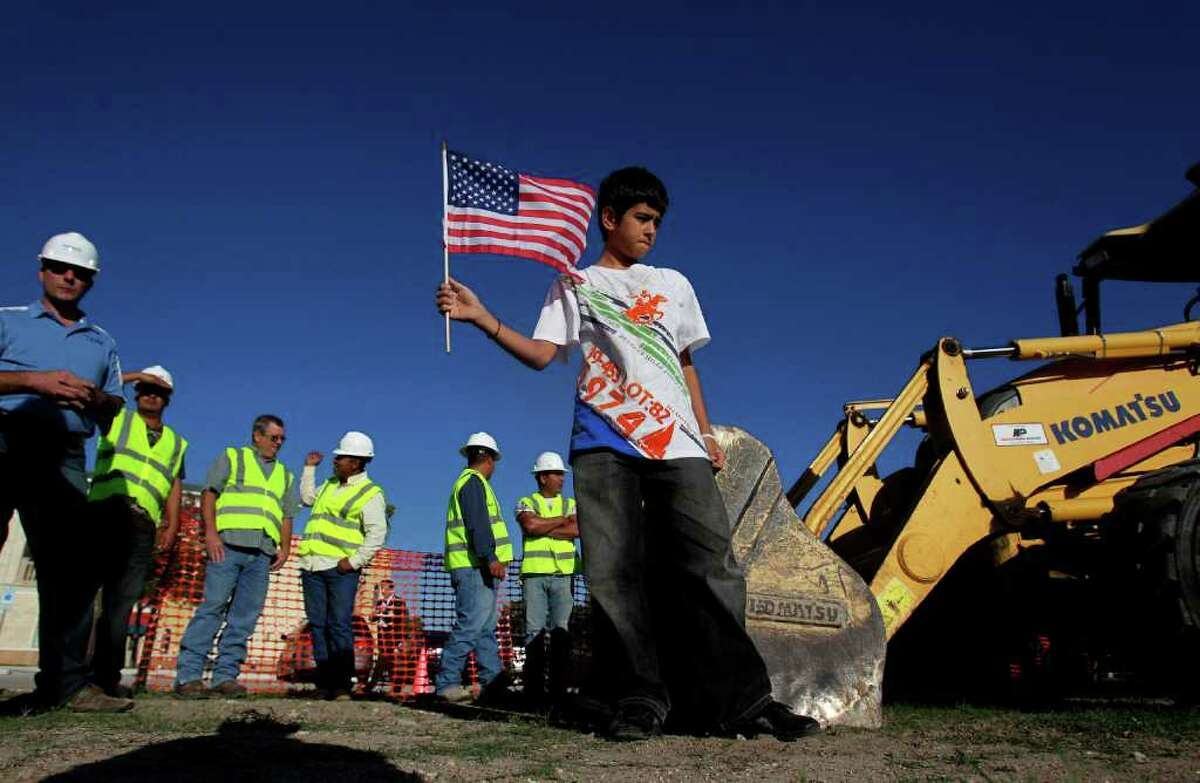 Next to a group of construction workers, Ihsan Yaman, 11, of Houston, holds an American flag before the groundbreaking for the Interfaith Peace Garden at the The Institute of Interfaith Dialog.