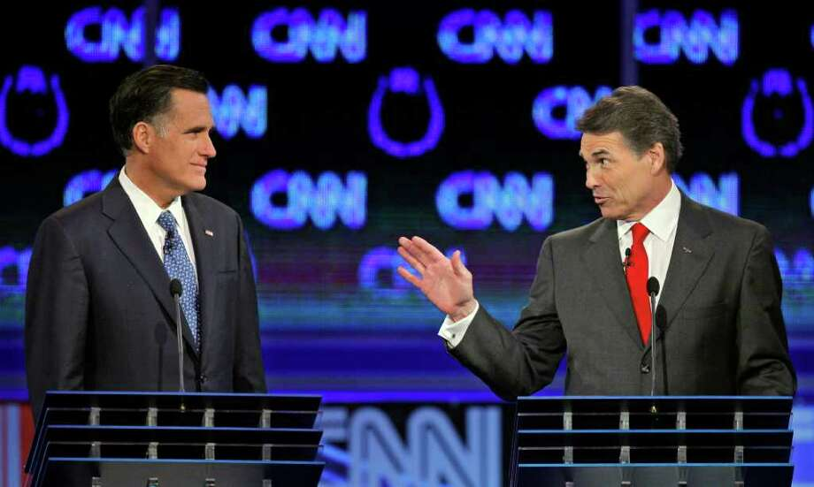 Republican presidential candidates Texas Gov. Rick Perry, right, speaks to former Massachusetts Gov. Mitt Romney during a Republican presidential debate Tuesday, Oct. 18, 2011, in Las Vegas.  (AP Photo/Chris Carlson) Photo: Chris Carlson