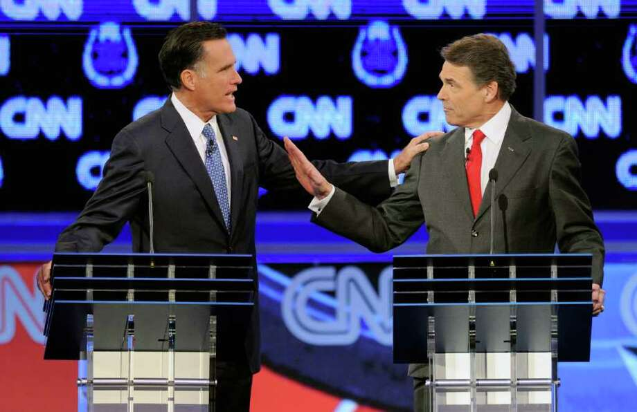 ETHAN MILLER : GETTY IMAGES HAND-TO-HAND COMBAT: Mitt Romney and Texas Gov. Rick Perry interrupted each other repeatedly on the issue of immigration, one of several vigorous clashes they had. Photo: Ethan Miller / 2011 Getty Images
