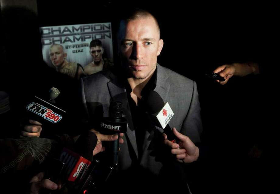 In this Tuesday, Sept. 6, 2011 photo, UFC welterweight champion Georges St. Pierre speaks to reporters during a press conference in Toronto. A knee injury suffered in training Tuesday has forced St. Pierre out of next week's UFC 137 title fight with Carlos Condit. (AP Photo/The Canadian Press, Darren Calabrese) Photo: Darren Calabrese / CP