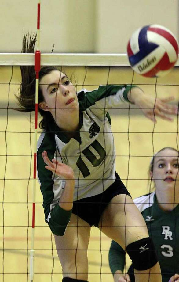 Reagan's Dayna Kramer (10) clears a shot against Madison as teammate Katie Medell (03) looks on in volleyball at Littleton Gym on Tuesday, Oct. 18, 2011. Reagan defeated Madison in three straight games.  Kin Man Hui/kmhui@express-news.net Photo: Kin Man Hui, ~ / San Antonio Express-News