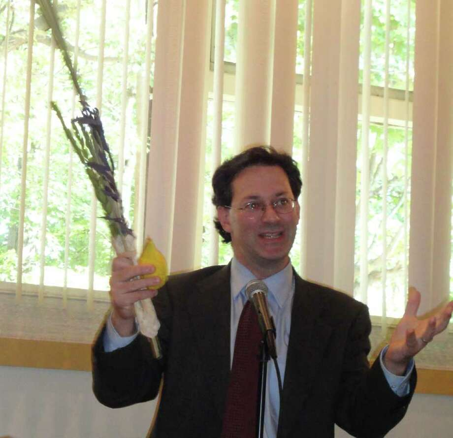 Congregation Beth El Rabbi Daniel J. Satlow provides information on the Jewish holiday of Sukkot to a group of about 180 people who attended the 37th annual Interfaith Sukkot Luncheon at the synagogue Tuesday. He holds a lulav, the youngest shoot or branch of a palm tree, a willow branch, myrtle branch, and an etrog, a fruit that resembles a lemon Photo: Meg Barone / Fairfield Citizen freelance
