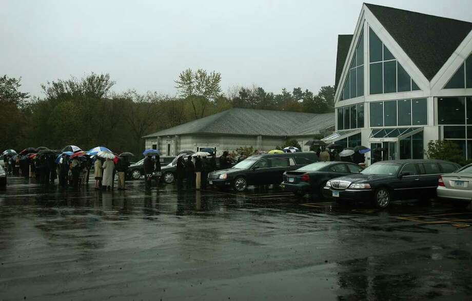 A long line of family, friends, teammates, and well wishers wait in the rain outside Crosss Street A.M.E. Zion Chuch in Middletown for the funeral of former Sacred Heart basketball player Chauncey Hardy on Wednesday, October 19, 2011. Photo: Brian A. Pounds / Connecticut Post