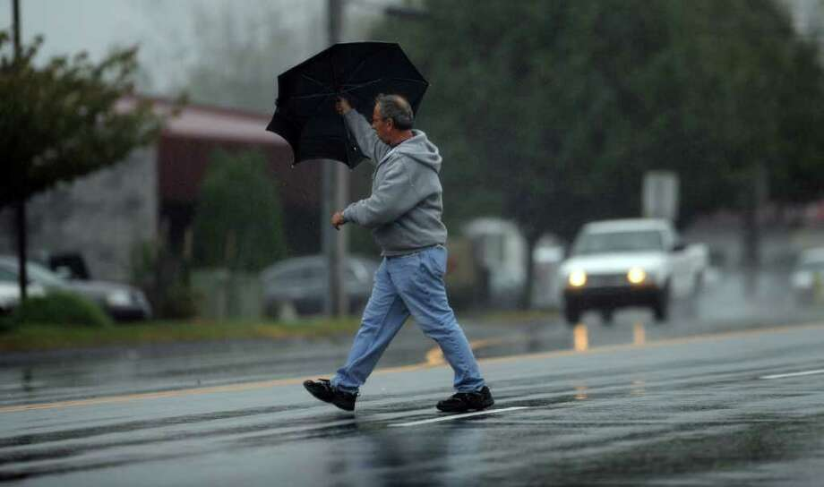 A man uses his umbrella as a shield from the wind and rain as he crosses Lordship Boulevard in Stratford Wednesday, Oct. 19, 2011. Photo: Autumn Driscoll