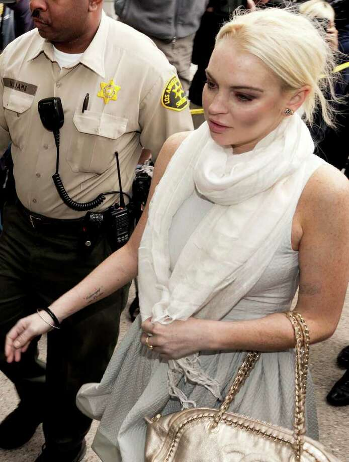 Lindsay Lohan arrives at the Los Angeles Superior Court West District Airport Courthouse Wednesday, Oct. 19, 2011, in Los Angeles. A city prosecutor will recommend Wednesday that the troubled starlet be sent back to jail because she had been ousted from a community service assignment at a women's shelter. Photo: Damian Dovarganes