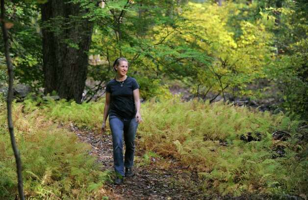 Lissy Newman, a board member of the Aspetuck Land Trust, walks along a fern-lined path at the new Newman Poses land preserve, part of the Aspetuck Land Trust in Westport, Conn. Photo: Autumn Driscoll