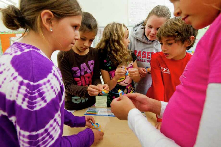 On  Wednesday Oct 20, 2011, Devyn O'Gorman, Andy Bandres, Olivia Birittieri, Katie Palamarcuik, Lance Large and Layla Riddle students in Melissa Velez's fifth-grade class at Glenville Elementary School in Greenwich, Conn. assembled ribbon pins for an Abilis benefit to be held at Tod's Point  on Sunday Oct. 23, 2011. Photo: Douglas Healey, Douglas Healey/Greenwich Time / Greenwich Time