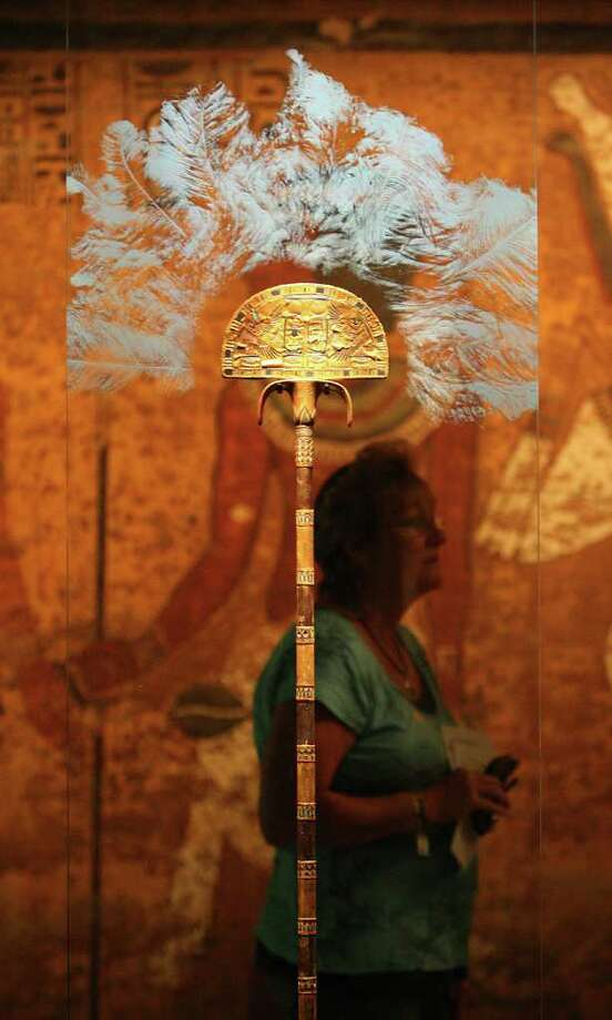 A woman walks by a fan (one of eight found in Kind Tut's tomb) with a hologram of feathers above it during the first day of Tutankhamun: The Golden King and the Great Pharaohs exhibit, at the Museum of Fine Arts, Houston,  Sunday, Oct. 16, 2011.   The exhibition will be on view through Sunday, April 5, 2012. ( Karen Warren / Houston Chronicle ) Photo: Karen Warren / © 2011 Houston Chronicle