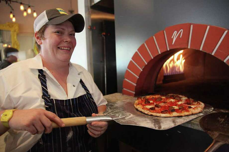Chef Brandi Key serves up a pizza out of an oven at Coppa. Photo: Mayra Beltran / © 2011 Houston Chronicle