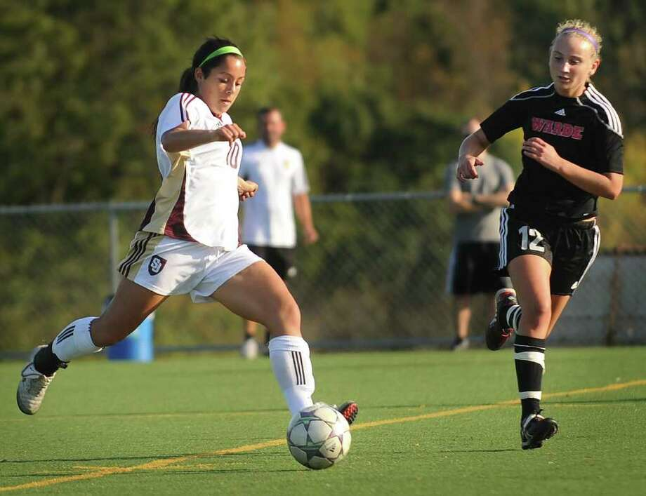 St. Joseph's Alyssa Christo, left, races the ball upfield againstand Fairfield Warde defender Maggie Allen. Christo is second in the region in scoring with 30 points, including 11 goals, for the undefeated Cadets (12-0-1). Photo: Brian A. Pounds / Connecticut Post