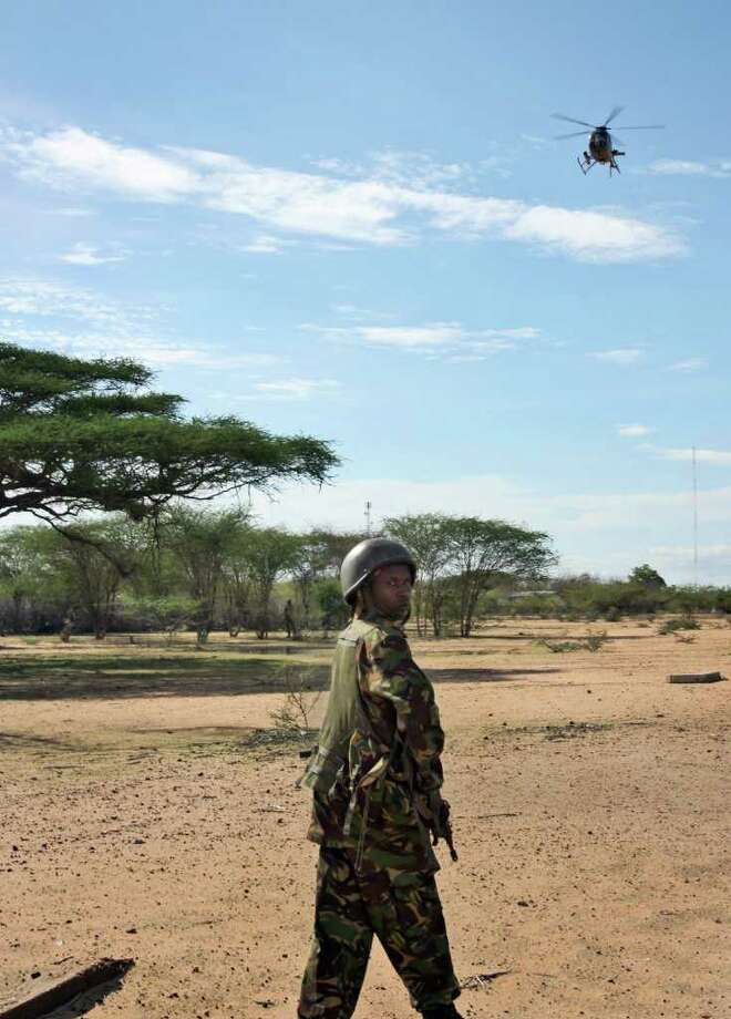 A member of the Kenyan military is seen near Liboi as a Kenyan military helicopter flies overhead at the border with Somalia in Kenya, Tuesday, Oct. 18, 2011. Kenya said its launch of military operations into southern Somalia against al-Shabab militants was in response to the kidnappings of four Europeans over the last six weeks, though military analysts suspect that Kenya had prepared the invasion before the abductions. (AP Photo) / AP