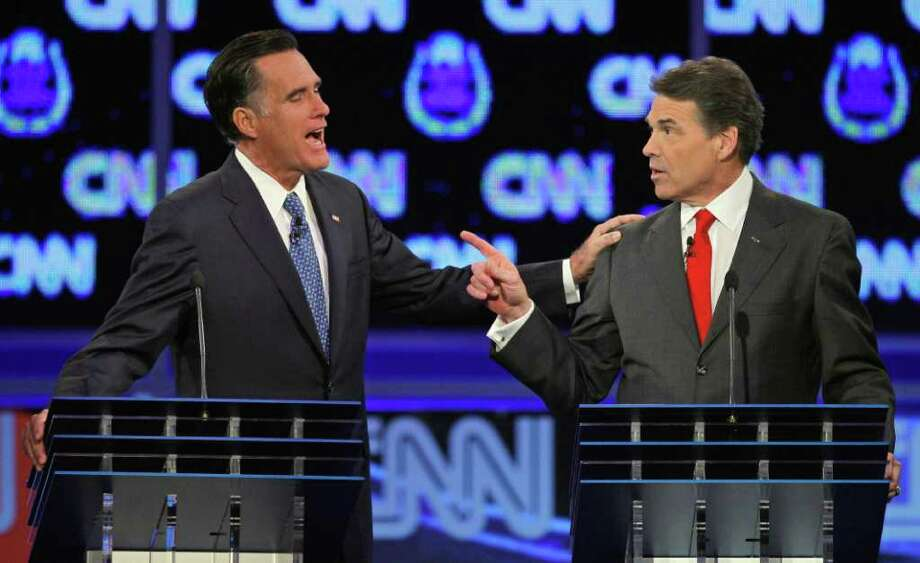 FILE - In this Oct. 18, 2011 file photo, Republican presidential candidates, former Massachusetts Gov. Mitt Romney, left, and Texas Gov. Rick Perry, speak during a Republican presidential debate in Las Vegas. The image of Romney laying a hand on Perry's shoulder may well be remembered long after people have forgotten that the two were squabbling about. Body language speaks volumes in political debates.  (AP Photo/Chris Carlson, File) Photo: Chris Carlson / A