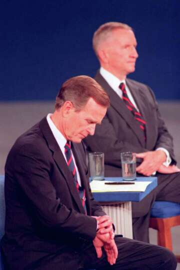FILE - In this Oct. 15, 1992 file photo, President George H.W. Bush looks at his watch during a pres