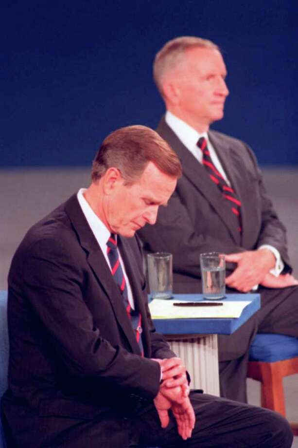 FILE - In this Oct. 15, 1992 file photo, President George H.W. Bush looks at his watch during a presidential debate at the University of Richmond's Robins Center. Independent candidate Ross Perot is at rear. Body language speaks volumes in televised debates. Classic moments from debates past often had more to do with what the candidates did _ or didn't do _ than what they said. (AP Photo/Ron Edmonds, File) Photo: Ron Edmonds / ap