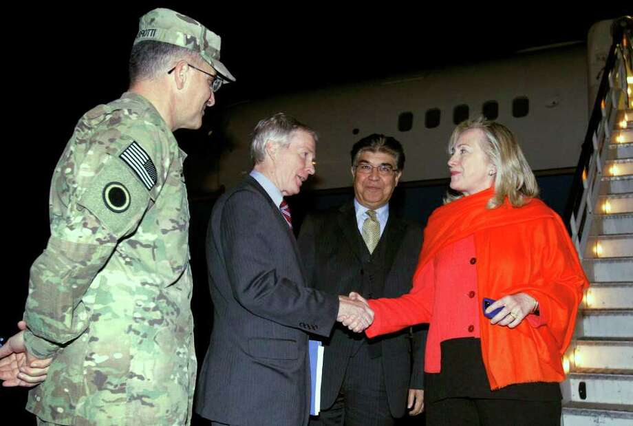 KEVIN LAMARQUE: AFP/GETTY IMAGES DROPPING IN: Secretary of State Hillary Rodham Clinton is greeted Wednesday by U.S. Ambassador Ryan Crocker as she arrives on a surprise visit to Kabul. Clinton is to meet Thursday with President Hamid Karzai to urge him to pursue peace talks with the Taliban ahead of international conferences later this year. Also on hand are Lt. Gen. Curtis Scaparotti, left, and Afghan chief of protocol Hamid Saddiq. Photo: KEVIN LAMARQUE / AFP
