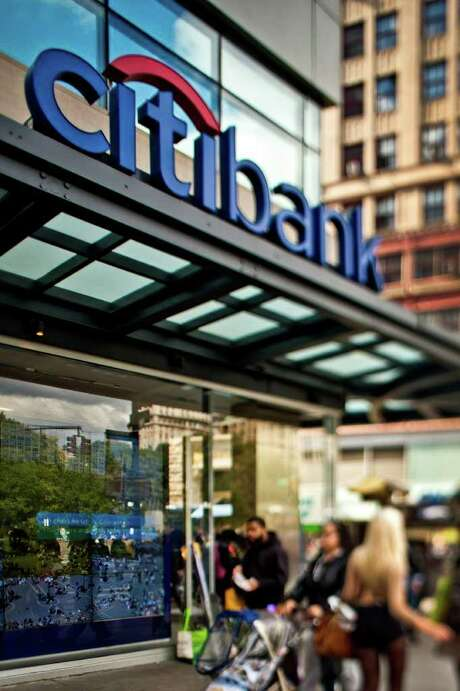 Chris Goodney : Bloomberg SETTLED: Pedestrians pass a Citibank branch in New York this week. The parent company, Citigroup, settled a civil fraud complaint that it misled investors. Photo: Chris Goodney / © 2011 Bloomberg Finance LP
