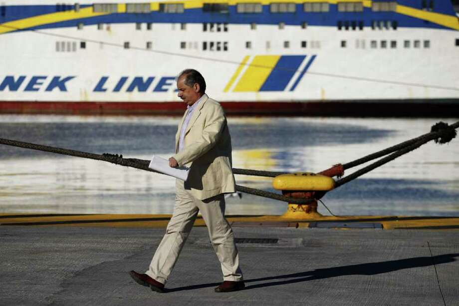 A man walks in front of  docked ships during a strike in the port of Piraeus, near Athens, on Wednesday, Oct. 19, 2011. A two-day general strike that unions vow will be the largest in years grounded flights, disrupted public transport and shut down everything from customs offices to shops and schools in debt-ridden Greece on Wednesday.(AP Photo/Petros Giannakouris) Photo: Petros Giannakouris / AP