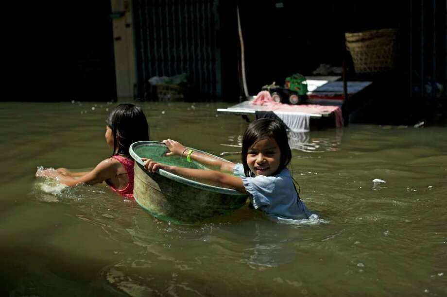 NICOLAS ASFOURI: AFP/GETTY IMAGES SURVIVING: A girl holds on to a plastic bowl Wednesday as she makes her way through floodwaters in suburban Bangkok. Photo: NICOLAS ASFOURI / AFP