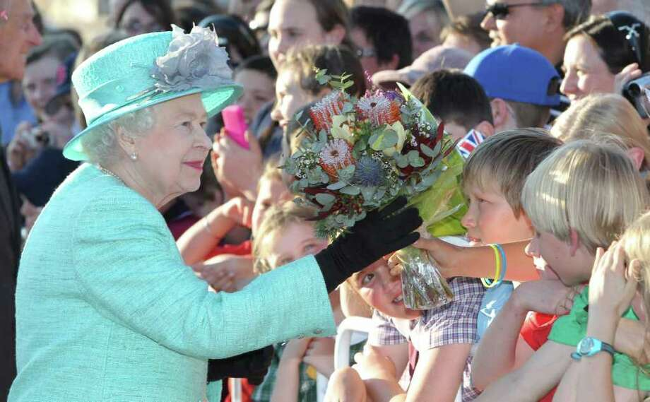 Queen Elizabeth II receives gifts from the crowd on arrival at Canberra airport on October 19, 2011 in Canberra, Australia. The Queen and Duke of Edinburgh are on a 10-day visit to Australia and will travel to Canberra, Brisbane, Melbourne before heading to Perth for the Commonwealth Heads of Government meeting. This is the Queen's 16th official visit to Australia. Photo: Pool, Getty / 2011 Getty Images