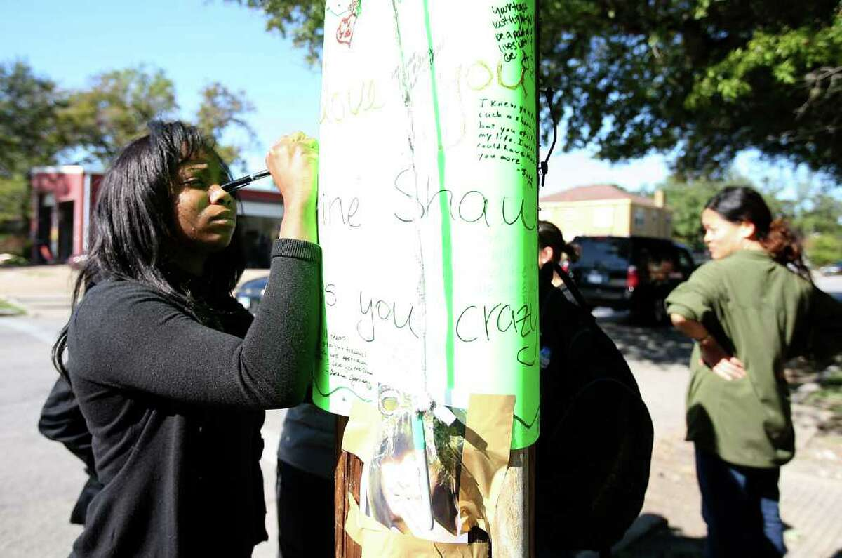 KAREN WARREN : CHRONICLE TRIBUTES: Eva Anassi writes a note on a poster board memorial for TSU law school student Halley Catherine Shaw, who was killed Tuesday night by a driver who fled the scene.